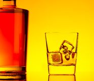 One glass of whiskey with ice cubes near bottle on table with reflection, warm tint atmosphere Royalty Free Stock Photos