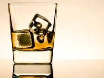 One glass of whiskey with ice cubes on table with reflection, light brown atmosphere Royalty Free Stock Image
