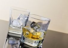 One glass of whiskey and one empty with ice cubes on black table with reflection Royalty Free Stock Photography