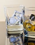 One glass of whiskey and one empty with ice cubes on table with reflection Royalty Free Stock Photo