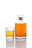 One glass of whiskey on the rocks, with a whiskey bottle in white background Royalty Free Stock Photography