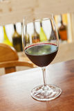 One glass of wine. On woody table  and bottles as background Royalty Free Stock Images