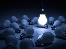 One glowing hanging light bulb standing out from the unlit dead incandescent bulbs with reflection , leadership and different Stock Image