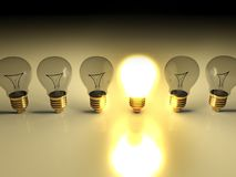 One glowing light bulb amongst other light bulbs Stock Photo
