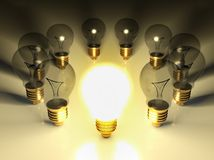 One glowing light bulb amongst other light bulbs Stock Photos