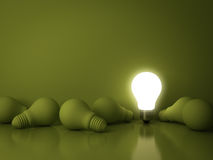 One glowing light bulb standing out from the dead incandescent bulbs on green background with reflection Royalty Free Stock Photography