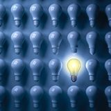 One glowing light bulb standing out from the unlit bulbs on dark blue background Royalty Free Stock Image
