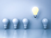 One glowing light bulb standing out from the unlit incandescent bulbs on blue background with reflection Royalty Free Stock Photography