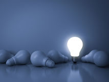 One glowing light bulb standing out from the unlit incandescent bulbs on blue background with reflection , individuality and diffe Stock Photography