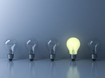 One glowing light bulb standing out from the unlit incandescent bulbs on blue background Royalty Free Stock Photo