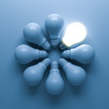 One glowing light bulb standing out from the unlit incandescent bulbs on blue Stock Photos