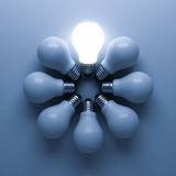 One glowing light bulb standing out from the unlit incandescent bulbs on blue background with shadow , individuality and different Royalty Free Stock Photography