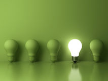 One glowing light bulb standing out from the unlit incandescent bulbs on green background with reflection Royalty Free Stock Photo