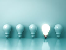 One glowing light bulb standing out from the unlit incandescent bulbs on green background with reflection Stock Image