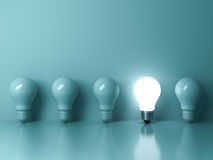 One glowing light bulb standing out from the unlit incandescent bulbs on green background with reflection Stock Photos
