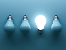 One glowing light bulb standing out from the unlit incandescent bulbs on green background Royalty Free Stock Photo