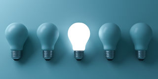 One glowing light bulb standing out from the unlit incandescent bulbs on green background Royalty Free Stock Image