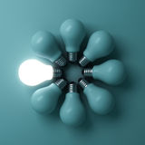 One glowing light bulb standing out from the unlit incandescent bulbs on green background Stock Photography