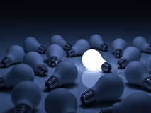 One glowing light bulb standing out from unlit incandescent bulbs with reflection on blue background Royalty Free Stock Photography