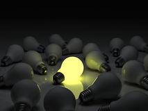 One glowing light bulb standing out from the unlit incandescent bulbs with reflection , individuality and different concept Stock Images