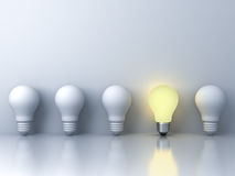 One glowing light bulb standing out from the unlit incandescent bulbs on white background Royalty Free Stock Photo