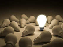 One glowing light bulb standing out from the unlit incandescent lightbulbs Royalty Free Stock Images