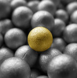 One Golden Ball. A background of silver balls with the focus on the golden one in the middle Stock Photos