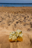 One golden christmas gift on beach Royalty Free Stock Image