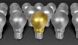 One golden light bulb among many silver ones on grey textured background Royalty Free Stock Image