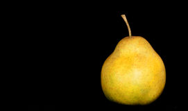 One Golden Pear. A ripe pear isolated on a black background stock photo