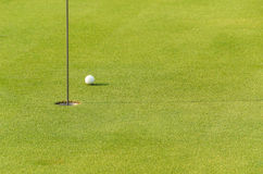 One golf ball near to hole. On green in morning light Royalty Free Stock Image