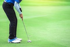 One golf player is putting a putter to the ball to hit the hole. To reach the goal Stock Photography