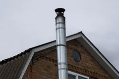 Gray long metal pipe chimney on a brown brick loft against the sky royalty free stock image