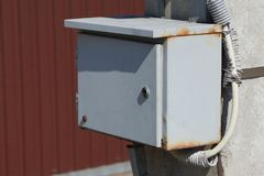 Gray metal box for electricity on a pole outside. One gray metal box for electricity on a pole outside stock image