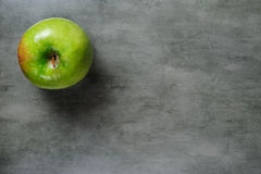 One green apple on dark stone background, top view. Stock Images