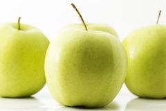 One green apple in front of three. Green apples on white background royalty free stock photos