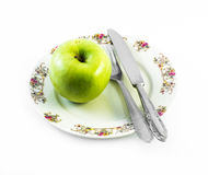 One green apple with knife and fork on a white plate with decorations and white background Royalty Free Stock Images