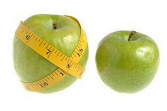 One green apple wrapped with measuring tape and another green ap. Ple isolated on white Stock Photography