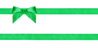One green bow knot on two parallel silk ribbons Royalty Free Stock Photo