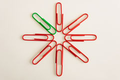 One green clip in group of red clips Royalty Free Stock Photography