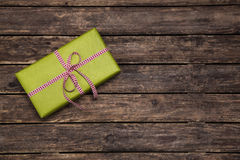One green gift box wrapped in apple green box with red white che. One green present with checked ribbon on wooden rustic background for publicity royalty free stock photos