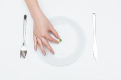 One green pea on the plate taken by woman hand Stock Photo