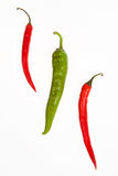 One green and two red peppers. On a white background Royalty Free Stock Photo