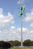 One Green Urban Wind Turbine. Fort Lauderdale, FL, USA - May 16, 2017: Green color power generating wind turbine near a park lake. Unusual vertical access wind Stock Photos
