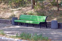 Green wooden bench with bins stand on the asphalt in the park royalty free stock photography