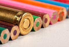 One gun bullet together with pencils Royalty Free Stock Image