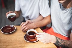 Two males tasting mugs of beverage indoor. One guy holding hand of another man. They sitting at table and drinking cups of appetizing coffee royalty free stock images