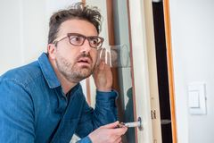 Man portrait listening and spying through the wall royalty free stock image