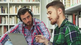 Two cute guys spend their free time in the library. One guy looks something on the laptop. The second sits next to him and listens to music. The first guy found royalty free stock photo