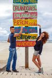 One guy and redhead girl possing over directions signpost. One guy and redhead girl possing over directions signpost on the beach Stock Image